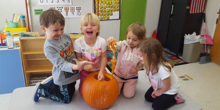 Preschoolers carving pumpkins